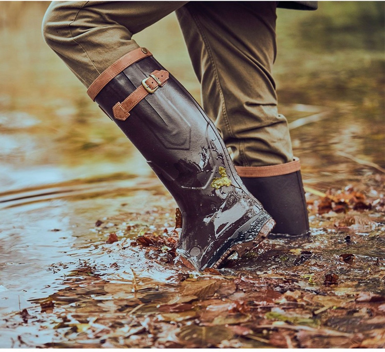 A person wearing a pair of wellington boots walking through a puddle.