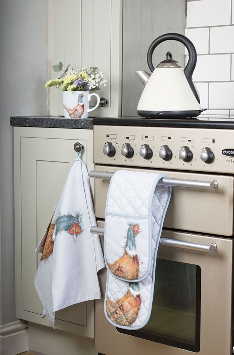 The tea towel and oven gloves from Wrendale Pheasant Gift Set hanging off of a cupboard and over handle.
