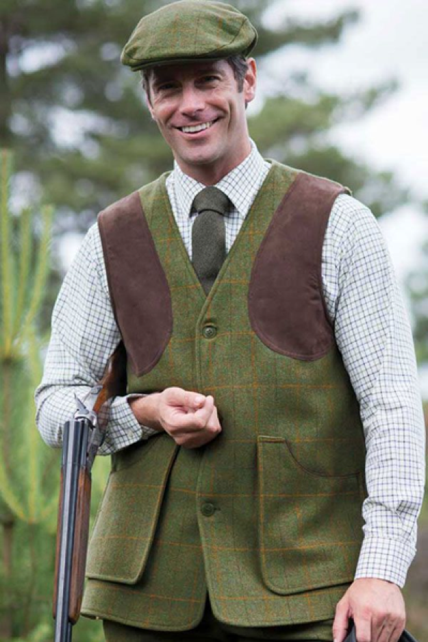 A man wearing Alan Paine Combrook Shooting Vest Lovat and a tweed cap.