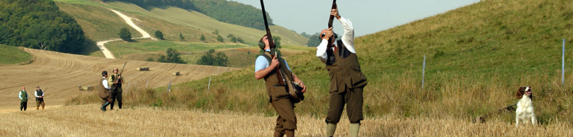 Men with their gundogs holding their guns up towards the sky