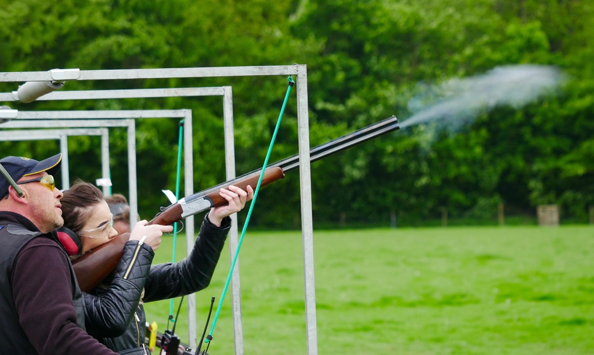 Lady shooting a gun in an field