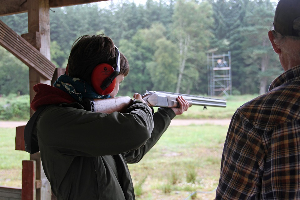Woman learning clay pigeon shooting