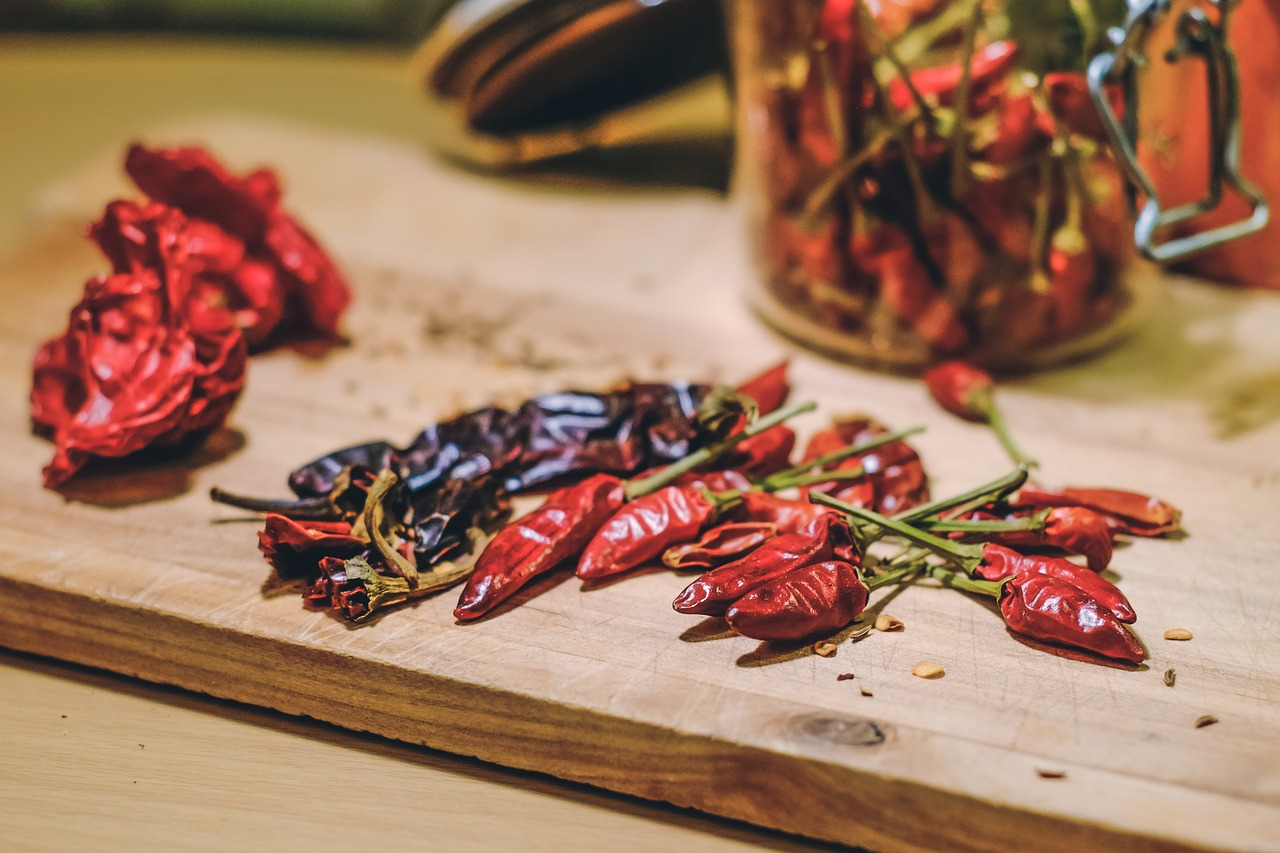 A selection of chillies on a chopping board in a kitchen.