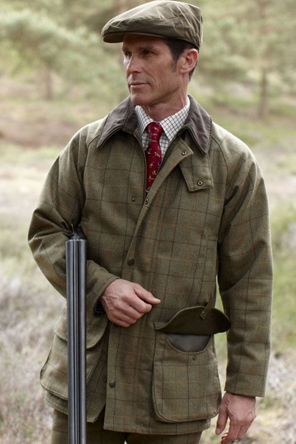 A man wearing a tweed cap and jacket holding his gun ready for a day's shooting