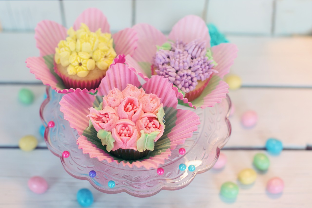 A selection of handmade cupcakes decorated with iced flowers.