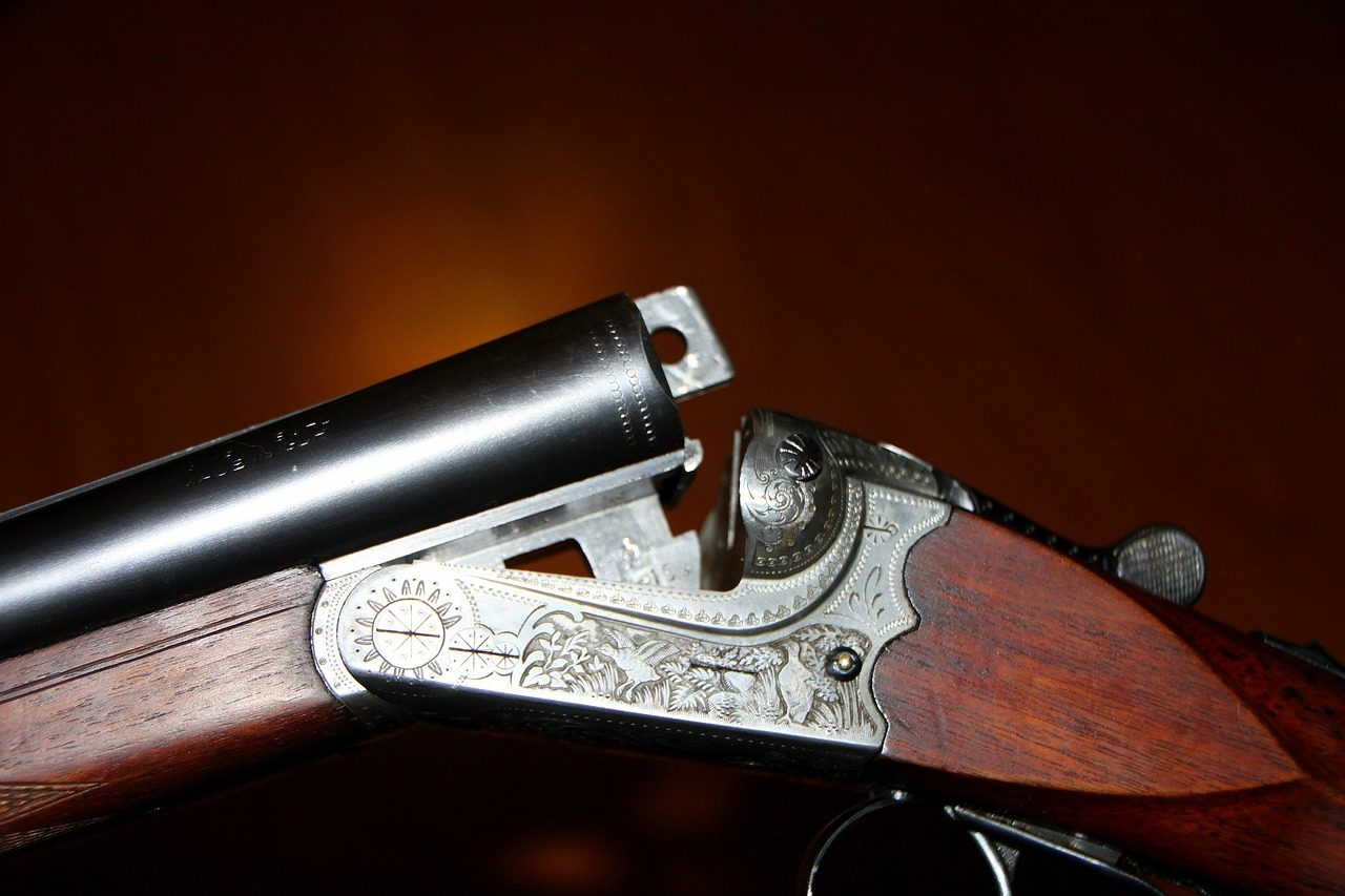 A shotgun with the barrel lifted away from the chamber and stock.