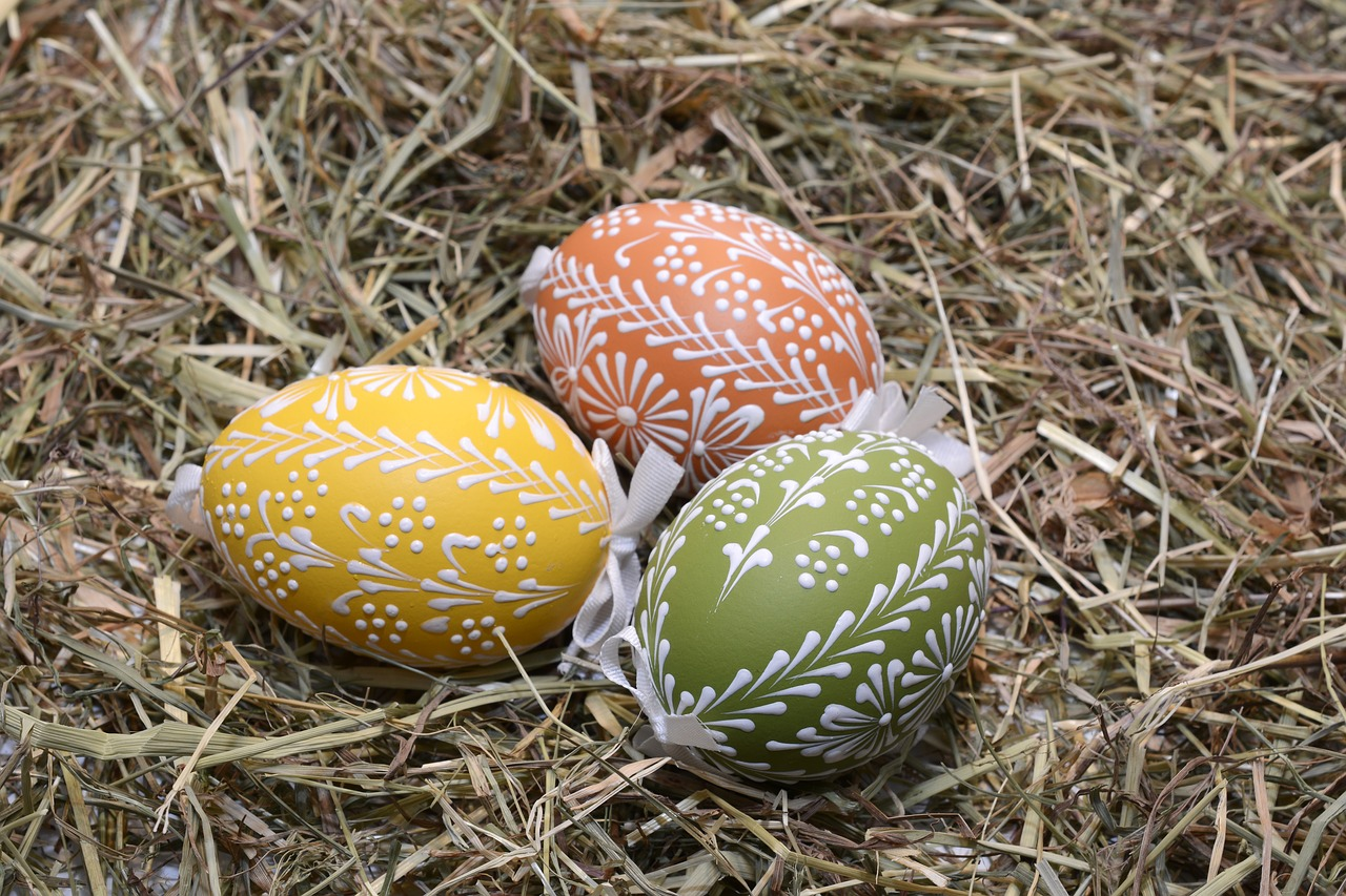 Three painted eggs with white detailing laid on a straw nest.
