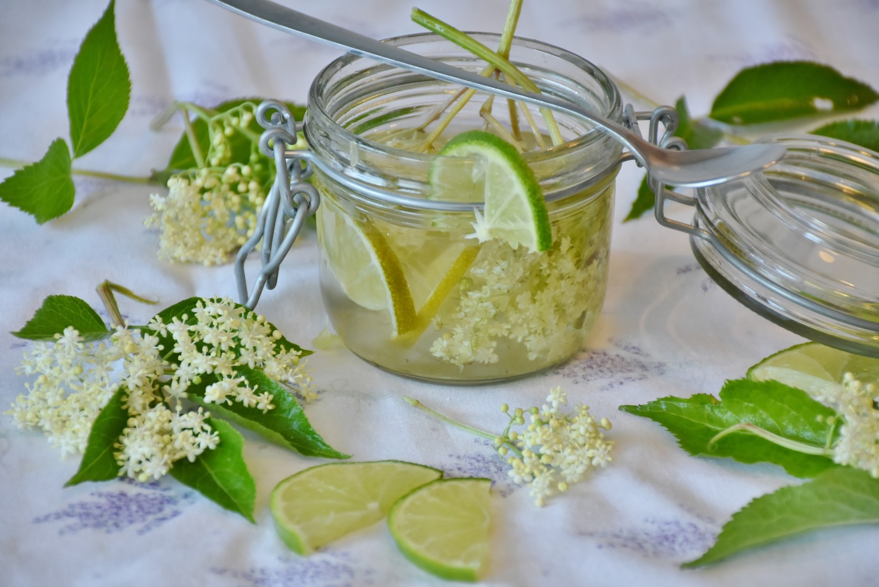Lime and elderflowers with a spoon on a posh jar