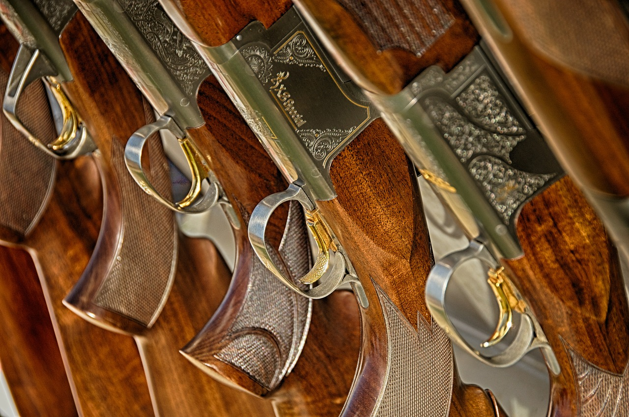 Shotguns lined up in a row on a stand at the British Shooting Show.