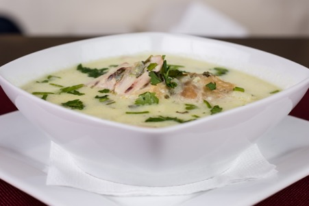 Chunky chicken soup with parsley on top.