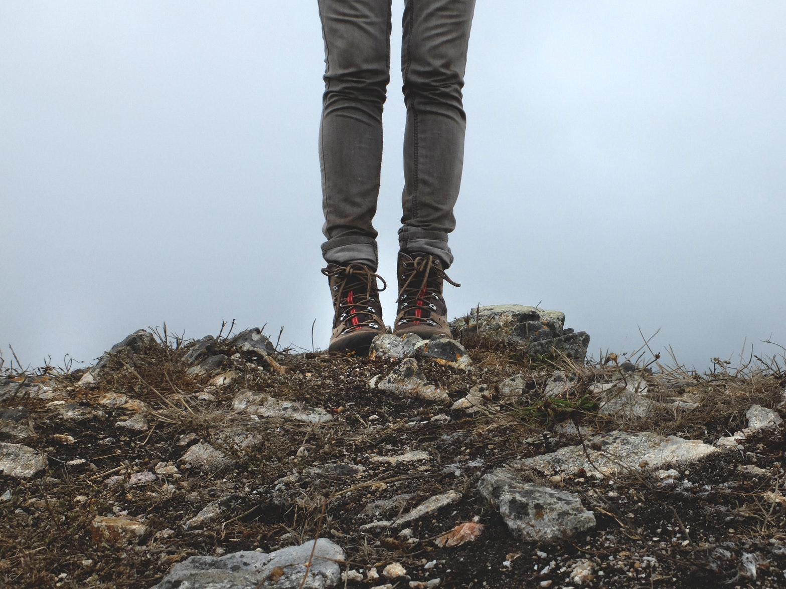 Woman wearing hiking boots standing on rocky path