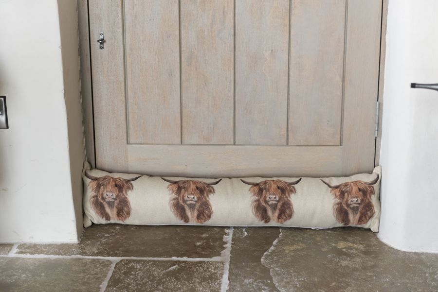 Draught excluder with highland cow design in front of a wooden door