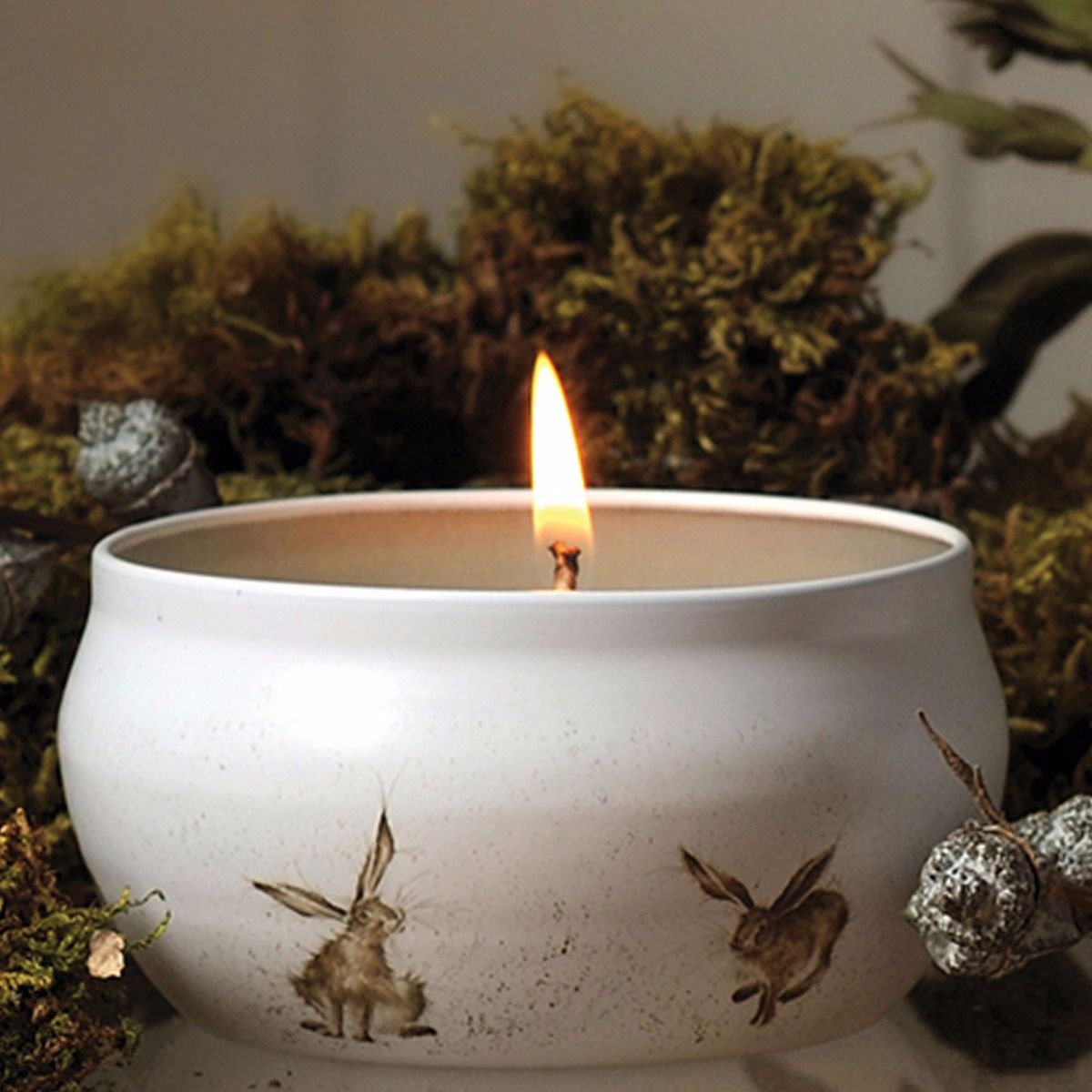 The Scented Bliss Candle Hare in front of some garden greenery.