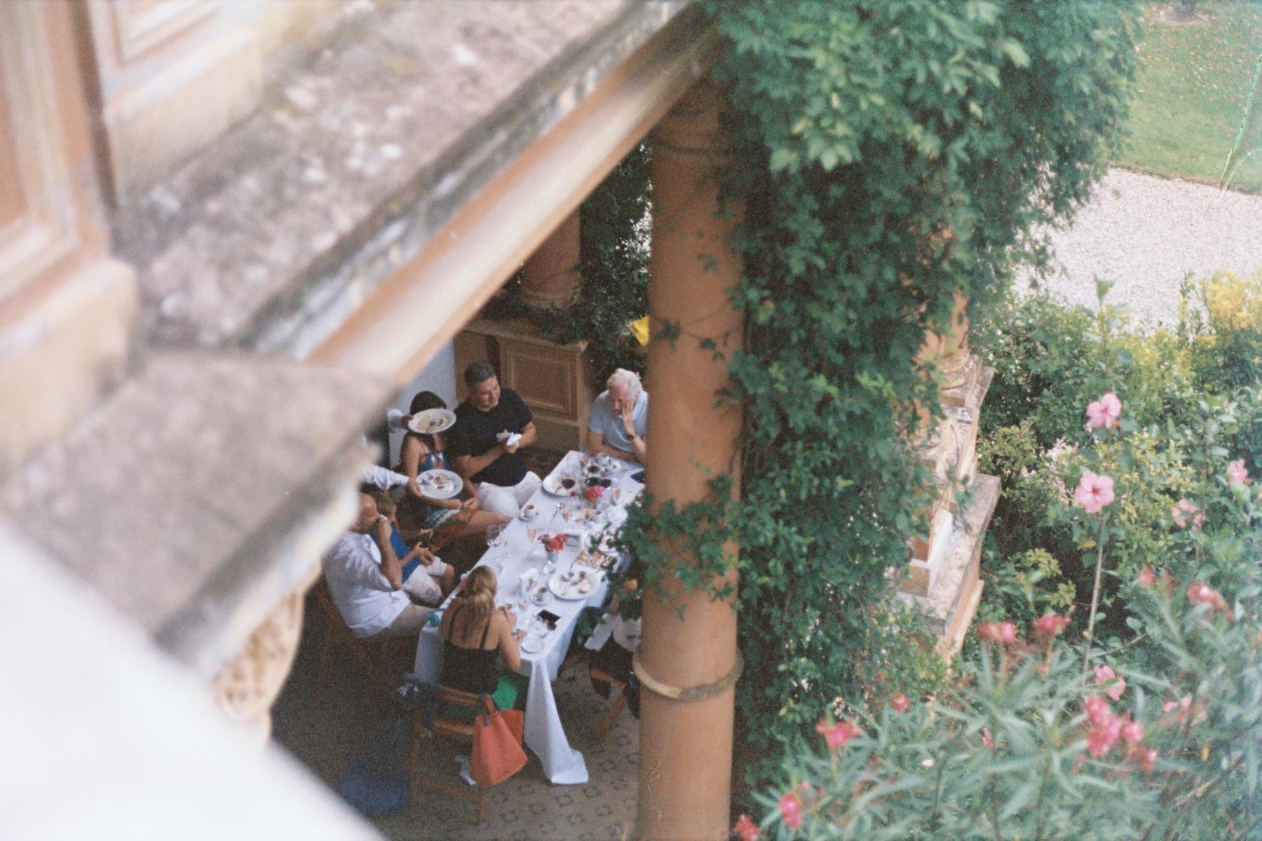 group of people in the garden enjoying dinner