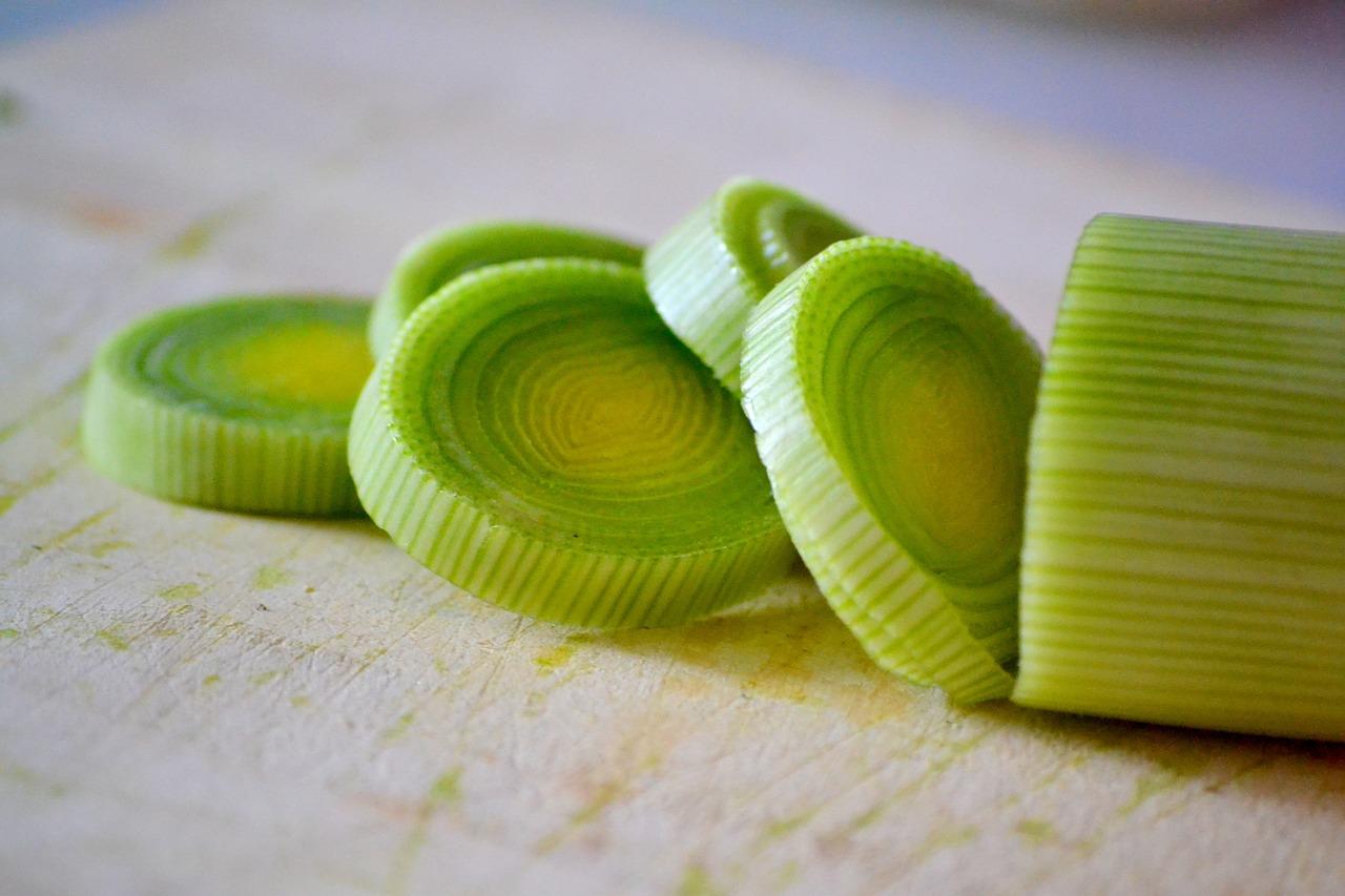 Chopped green leeks on a wooden board.