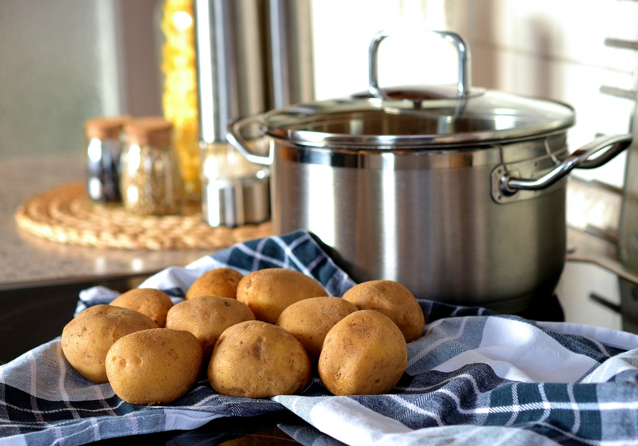 Some potatoes on tea towel in front of a large metal saucepan.