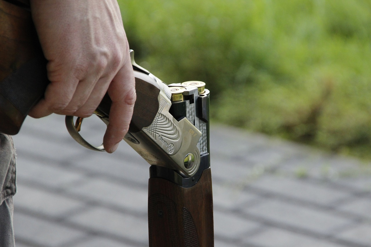 A person holding a loaded shotgun while standing on a paved area.