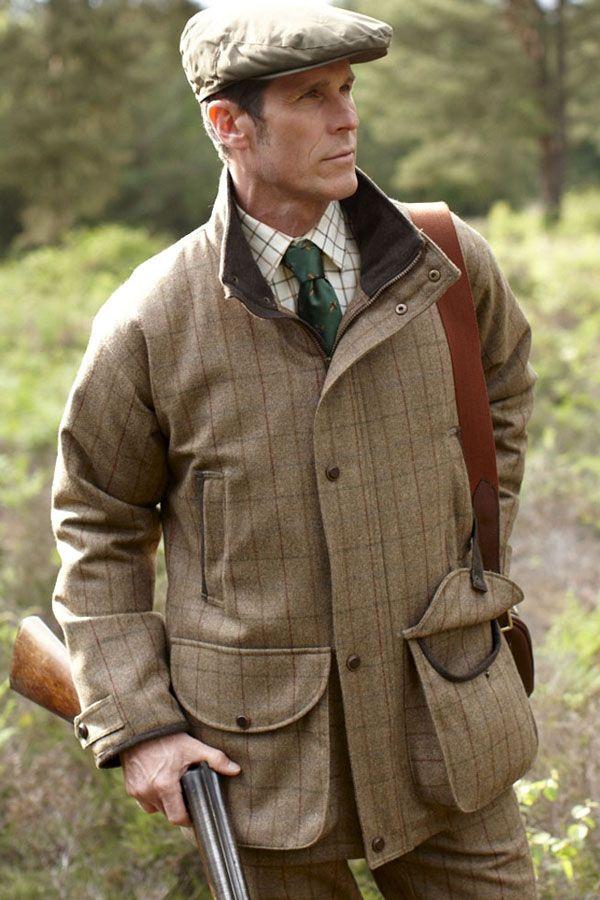 Man wearing brown tweed jacket holding a shotgun