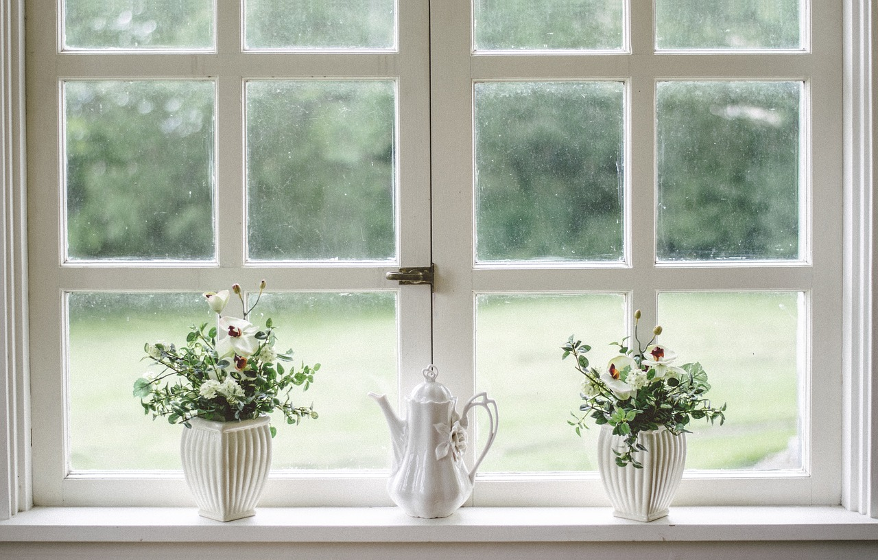 A windowsill with two white vases of flowers and a white teapot on it.